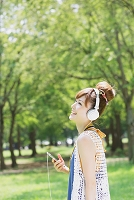 新緑と音楽を聴く日本人女性