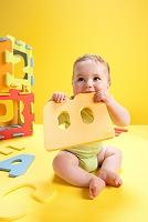 アルファベットのおもちゃをかじる赤ちゃん