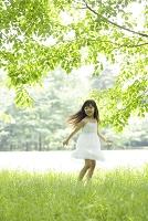 新緑の中の白いワンピースの日本人の女の子