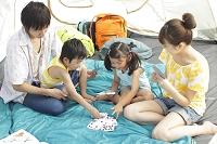 テントの中でトランプをする家族