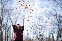 落ち葉を巻き上げる日本人女性