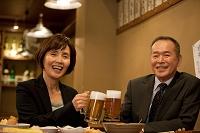 ビールで乾杯するビジネスマンとビジネスウーマン