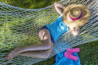 夏に日陰でハンモックに揺られる女の子