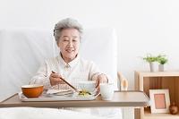 介護ベッドで食事をするシニア日本人女性