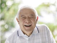 口を開けて笑うシニアの日本人男性