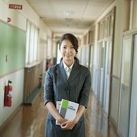 学校の廊下に立つ日本人女性教師