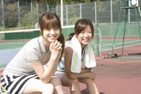 テニスコートのベンチに座っている女性