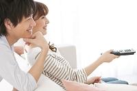 ソファーに座ってテレビを見るカップル