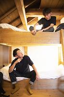 民泊の2段ベッドで過ごす若者
