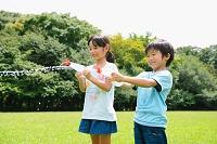 マヨネーズチューブの水鉄砲で遊ぶ小学生たち