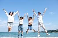 海辺でジャンプする家族