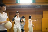 体育館でバレーボールの練習をする学生