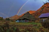 茅葺きの民家と虹
