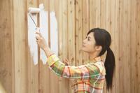 板壁をペンキで塗る女性
