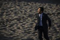 砂丘を歩く日本人ビジネスマン