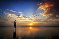 夜明けのビーチに立つ男性