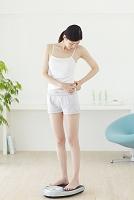 体重計に乗る若い女性