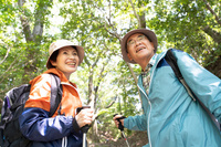 ハイキングをする日本人シニア夫婦