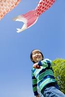 公園の鯉のぼりの下で遊ぶ日本人の男の子