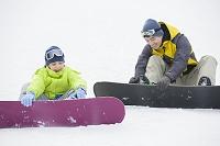 スノーボードをする親子