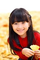 イチョウの葉を持つ笑顔の女の子