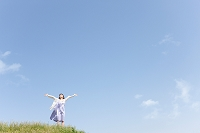 空を見上げて腕を広げる女性