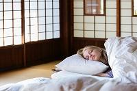 布団で寝ている若い女性