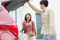トランクを開ける男性と買い物袋を持つ日本人女性