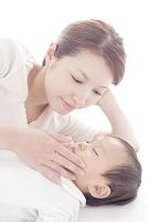 眠る赤ちゃんを見つめる母