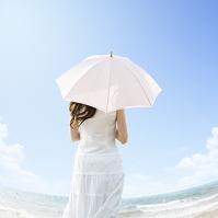海辺で日傘をさす女性の後ろ姿