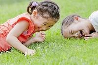 公園で寝転んで遊ぶ小学生