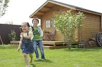 ログハウスの庭で遊ぶ男の子と女の子