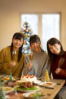クリスマスパーティーでシャンパングラスを持ち微笑む日本人女性