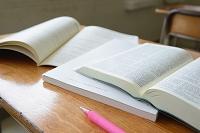 教室の机に置かれた筆記用具と教科書