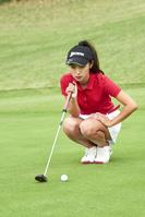 パッティングラインを読む女子ゴルフ選手