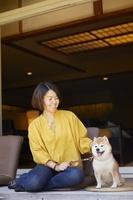 旅館の縁側でくつろぐ日本人女性と豆柴