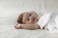 まっ白なタオルをかぶる裸の赤ちゃん