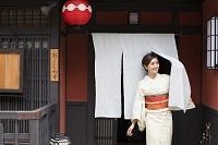 のれんから出てくる着物の日本人女性