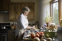 キッチンで野菜を洗うシニア女性