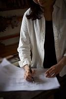 図面に書き込む女性