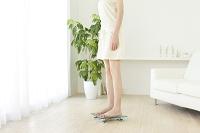 体重計に乗る若い女性の下半身