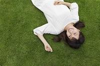 芝生で寝転ぶ若い日本人女性
