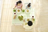 ダイニングテーブルで食事をする家族の俯瞰写真