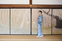 襖絵の前に立つ着物の日本人女性