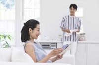 ソファに座って読書する日本人女性とキッチンでお皿を拭く男性