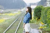 ホームで列車を待つ若い日本人女性