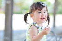 ベンチに座り上を見あげている日本人の女の子