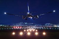 きらめく夜の空港に着陸するボーイング777 ANA 伊丹空港