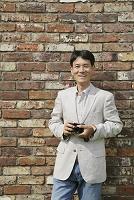 壁の前でカメラを持って立つ中年日本人男性