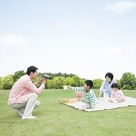 家族をビデオカメラで撮影する父親